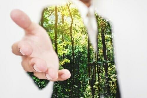 Nachhaltigkeit im Unternehmen-Mann im grünen Anzug streckt Hand aus.